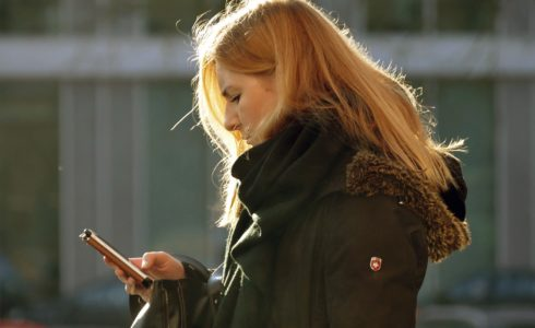 Frau schaut verärgert auf ihr Mobiltelefon