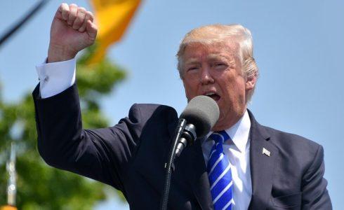 Donald Trump spricht in ein Mikrofon.